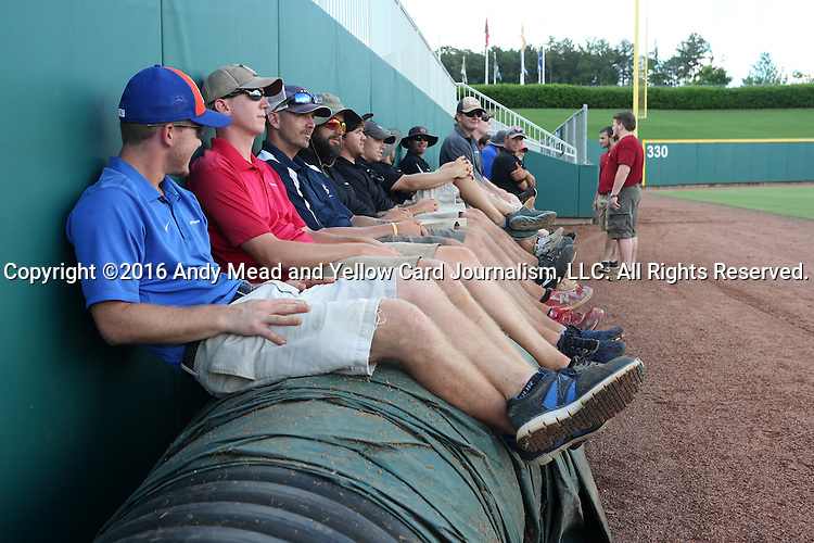 31 May 2016: Members of the stadium grounds crew sit on the tarp waiting for the word to roll it out onto the field. The Nova Southeastern University Sharks played the Lander University Bearcats in Game 8 of the 2016 NCAA Division II College World Series  at Coleman Field at the USA Baseball National Training Complex in Cary, North Carolina. Nova Southeastern won the game 12-1.