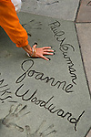 A visitor compares hand size with Paul Newman in the courtyard at Hollywod's famous Chinese Theater.