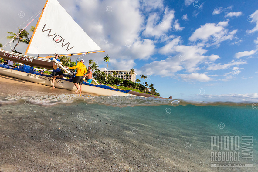 An over-and-under image of Ka'anapali Beach and a Hawaiian sailing canoe, Maui.