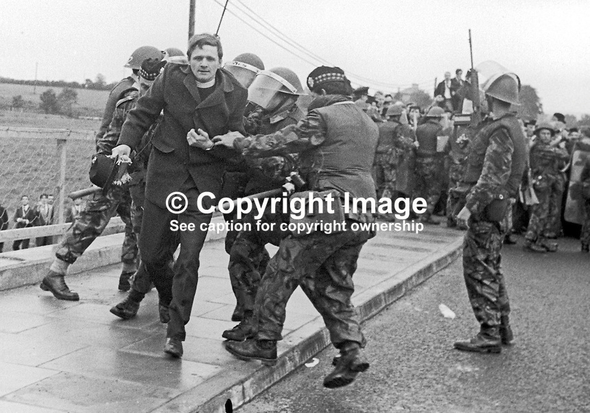Army &amp; police were in strength on the outskirts of Dungiven, Co Londonderry, to enforce a government ban on an Orange parade through the predominently Nationalist town on 13th June 1971. A prominent loyalist activist, Rev William McCrea, is hustled away by soldiers. 197106130220d<br />