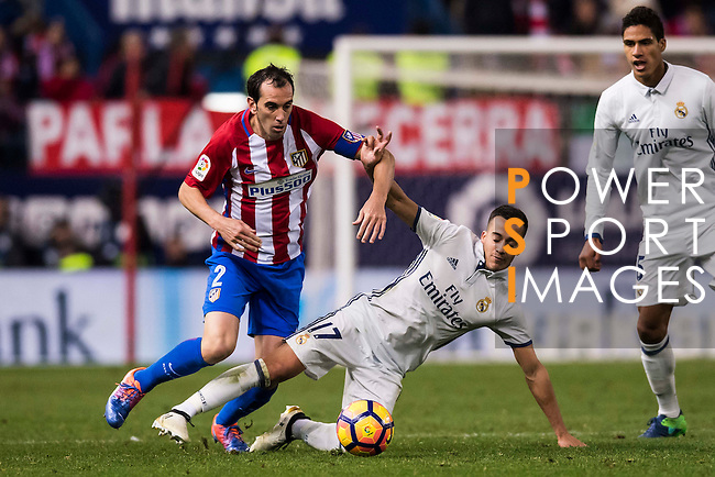 Lucas Vazquez of Real Madrid competes for the ball with Diego Roberto Godin Leal of Atletico de Madrid during their La Liga match between Atletico de Madrid and Real Madrid at the Vicente Calderón Stadium on 19 November 2016 in Madrid, Spain. Photo by Diego Gonzalez Souto / Power Sport Images