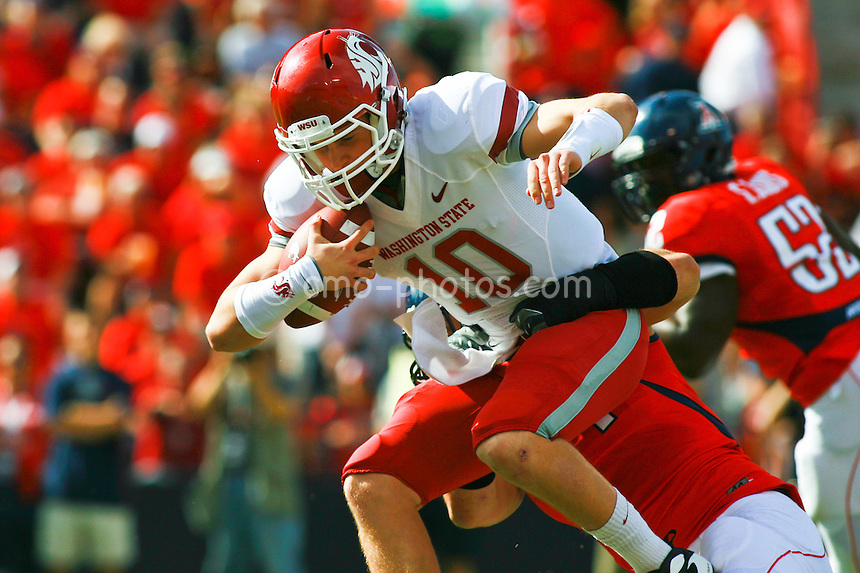 Nov 7, 2009; Tucson, AZ, USA; Washington State Cougars quarterback Jeff Tuel (10) is sacked by Arizona Wildcats defensive end Ricky Elmore (44) during the 1st quarter of a game at Arizona Stadium.  The Wildcats defeated the Cougars 48-7.