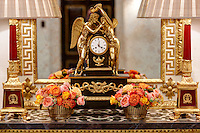 A pair of matching table lamps and two small arrangements of flower are displayed with an ornate clock mounted with two gold figures of angels. They stand on a console table with a gilt mirror behind.