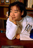 Korean physician doctor age 29 thinking at desk in office.  St Paul Minnesota USA