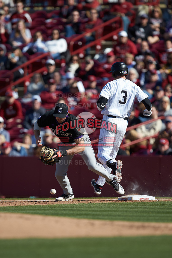 Alex Volpi (15) of the South Carolina Gamecocks can't handle a low throw as Braylen Wimmer (3) of the South Carolina Gamecocks crosses first base at Founders Park on February 15, 2020 in Columbia, South Carolina. The Gamecocks defeated the Crusaders 9-4.  (Brian Westerholt/Four Seam Images)