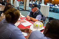Jim Ellis, an Air Force and Navy veteran from Danvers, Massachusetts, speaks with representatives of the Boston Fire Department at the Recovering Warrior Employment Conference at the Back Bay Event Center in Boston, Massachusetts, USA. Ellis said that he attended the conference to look for opportunities that fit his experience and expertise. &quot;I'd like to get in a position to help veterans,&quot; he said.<br /> <br />  The employment conference was organized by Hiring Our Heroes and Wounded Warrior Project. Hiring Our Heroes is an initiative of the US Chamber of Commerce Foundation. Approximately 40 veterans registered for the event, during which they had interviews with a number of different regional and national employers, including GE, Bank of America, Uber, and others.
