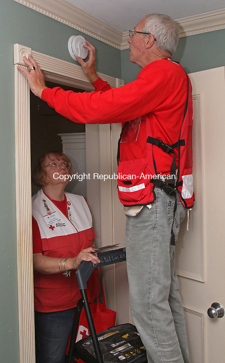 Southbury, CT-071815MK02 Volunteer Arthur Hopkins installs a smoke detector as fellow volunteer Teresa Folgel looks on in Roberta Hade's home at Heritage Village in Southbury Saturday morning.  Deborah Danen, American Red Cross territory-5 project manager, said that four teams set out to install multiple new smoke detectors in ten condos and each detector had a battery that will last ten years before having to be replaced.  Southbury's deputy fire marshal Derrek Guertin said that the department was on hand to give fire prevention tips and evacuation suggestions as part of the event.  The devices were provided at no charge to the homeowners from a program that American Red Cross receives funds for. Michael Kabelka / Republican-American.