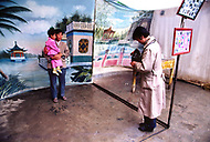 September, 1985. Shaanxi Province, China. People working in business establishments in Wuqi, such as this city photographer taking photos from local people.