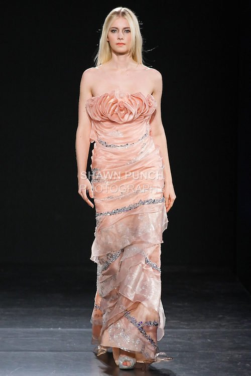 Model walks runway in an Edward Arsouni outfit, during Couture Fashion Week Fall 2011.