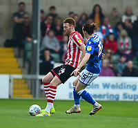 Lincoln City's Cian Bolger clears under pressure from Macclesfield Town's Ben Stephens<br /> <br /> Photographer Andrew Vaughan/CameraSport<br /> <br /> The EFL Sky Bet League Two - Lincoln City v Macclesfield Town - Saturday 30th March 2019 - Sincil Bank - Lincoln<br /> <br /> World Copyright © 2019 CameraSport. All rights reserved. 43 Linden Ave. Countesthorpe. Leicester. England. LE8 5PG - Tel: +44 (0) 116 277 4147 - admin@camerasport.com - www.camerasport.com