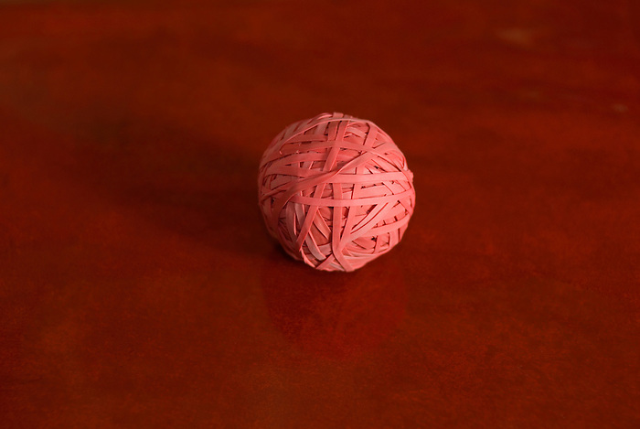 A ball made of red rubber bands on a red tablecloth.