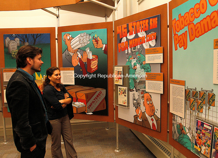 WINSTED, CT - 26 SEPTEMBER 2015 - 092615JW11.jpg -- Chris Miller and Jamie Rowen look at a display on cigarettes during the opening of the American Museum of Tort Law Saturday morning. Jonathan Wilcox Republican-American