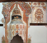 Chimney with frescoes of flowers in the Ceremonial reception room on the 3rd floor of the Zekate House, a grand fortified tower house built 1811-12 with twin towers and a great double arched facade, built and owned by Beqir Zeko, a general administrator of Ali Pasha's government, Gjirokastra, Southern Albania. This large and elaborately decorated room was used for the most important social occasions. The frescoes of garlands of fruits and flowers is typical of the Tulip period of Ottoman architectural design and has symbolic meanings for the health, wealth and abundance of the household. Gjirokastra was settled by the Greek Chaonians, the Romans and Byzantines before becoming an Ottoman city in 1417. Its old town was listed as a UNESCO World Heritage Site in 2005. Picture by Manuel Cohen