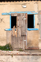 Dilapidated building with empty blue framed window and partial door frame leaning against it. Rzeczyca Central Poland