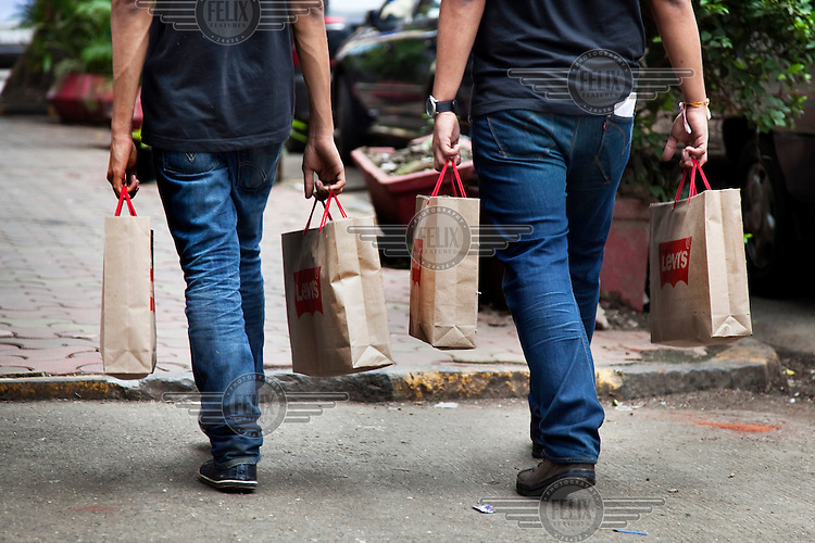 Two men carry shopping bags from Levi's, the American jeans company.  For many global fashion brands, the developing world, and India and particular, are their fastest growing markets. As a billion people begin to earn enough money to have disposable income, they are more likely to spend a higher portion of their incomes on such fashions.