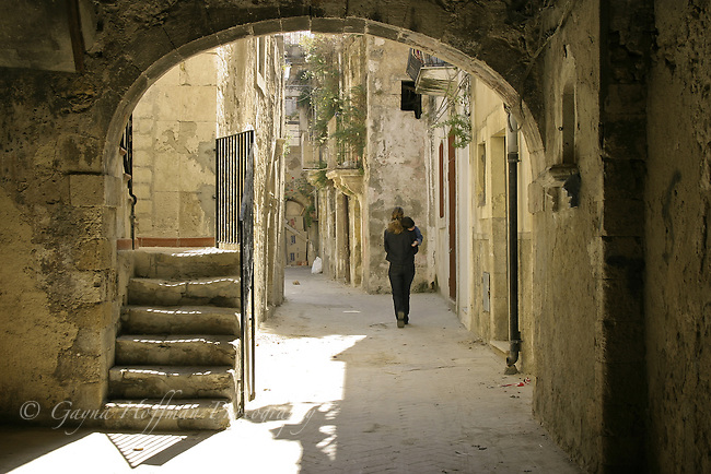 Woman carrying child, Arched alley. Sicily, Italy