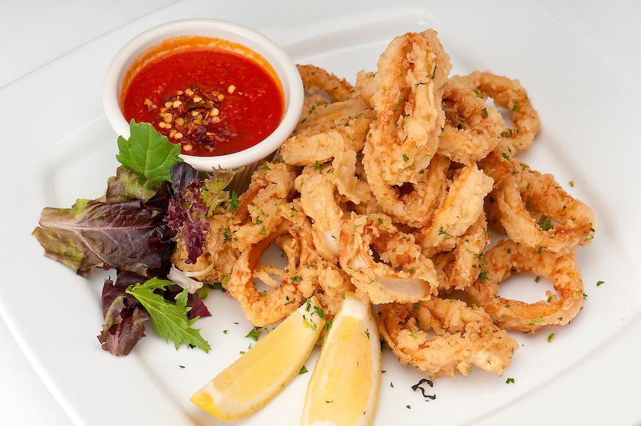 Plate of fried calamari served with marinara sauce and lemon.