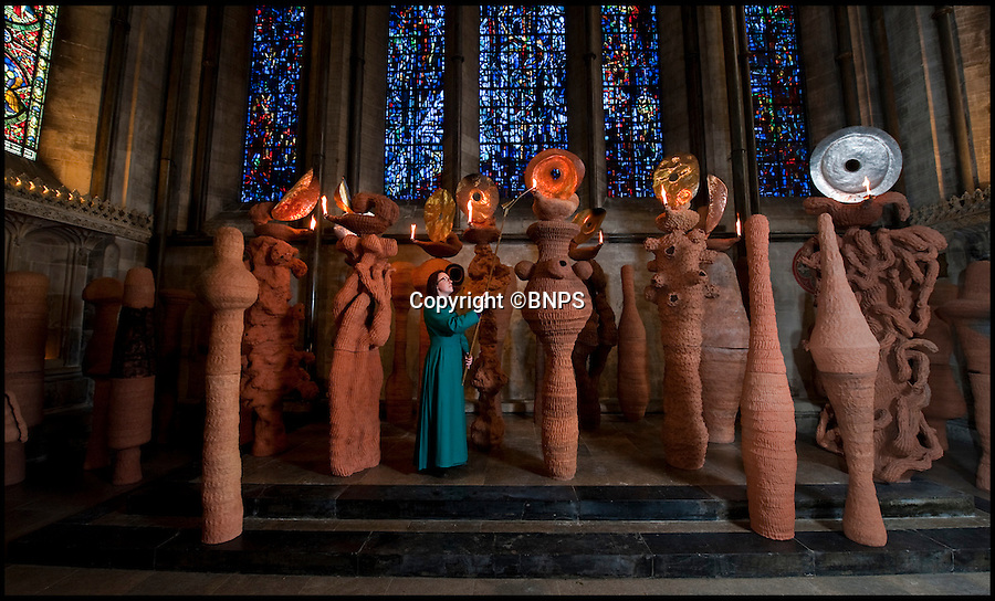 BNPS.co.uk (01202 558833)<br /> Pic: PhilYeomans/BNPS<br /> <br /> Verger Solveig Sonet carefully lights the oil lamps of acclaimed British artist Nicholas Pope's new installation in Salisbury Cathedral, 'The Apostle's speaking in Tongues'.<br /> <br /> The flames from the 12 terracotta 'apostles' represent the New Testament 'tongues of fire' speaking to the 19 other statues.<br /> <br /> The lamps on the 800 year old cathedral's high altar will be lit by the Vergers twice a day until August.