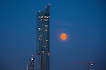"© Joel Goodman - 07973 332324 . 23/07/2013 . Manchester , UK . A blood red moon low over the skyline of Manchester , as seen tonight (23rd July 2013 ) with Manchester's iconic Beetham Tower in the foreground . The phenomenon can be caused by dust and pollution in the atmosphere and is most notable when the moon is low on the horizon as its light passes through a larger amount of atmosphere , which scatters blue light more than red . Biblical mythology makes several references to a red moon including , from Joel 2:31 , "" The sun shall be turned to darkness, and the moon to blood, before the great and awesome day of the Lord comes"" . Photo credit : Joel Goodman"