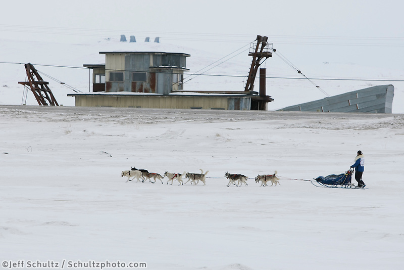 Friday  March 19, 2010    Musher Blake Freking runs on the Bering Sea with Swanberg's dredge and the old White Alice early warning site in the background 1 mile from the Nome finish .