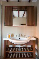 In the bathroom a simple wooden washstand has been constructed with a vanity mirror and cupboards to match