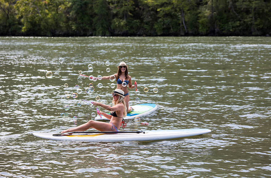 Two young attractive female SUP surfers on stand up paddle board have fun blowing bubbles in the middle of Lake Travis in Austin, Texas.
