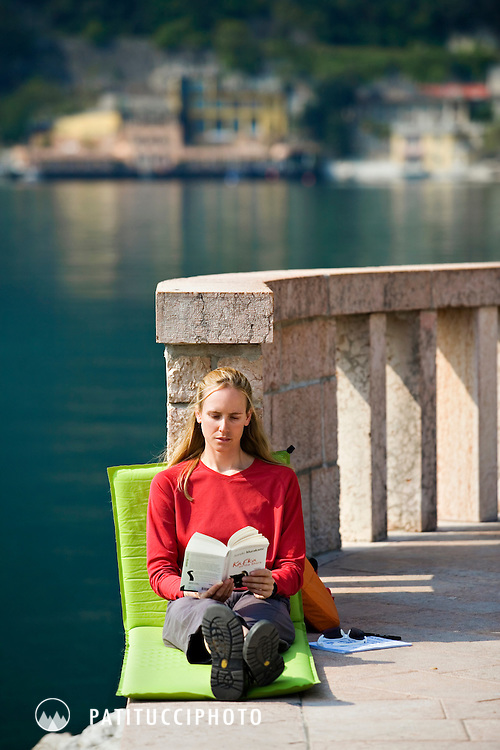 Amy Rasic reading a book and relaxing along the shore of Lake Garda, Italy