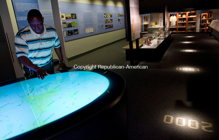 WATERBURY--09 June 08--060908TJ01 - Darryl Dilday, the director of security and building security at the Mattatuck Museum, demonstrates the Conversation Table at the museum's new, interactive exhibit that follows Waterbury history from the 17th century to the present day on Monday, June 9, 2007. The Conversation Table, which comes at the end of a timeline that snakes along the floor of the museum, displays statistical data from 1960 to 2000 over a map of Waterbury and surrounding towns to show the changes in areas such as income, household size, and manufacturing jobs. The museum will offer free admission for all on Saturday, June 14th, and will have guided tours of the interactive history exhibit at 10:30 a.m. and 2:30 p.m. (T.J. Kirkpatrick/Republican-American)