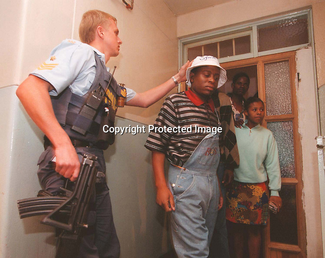 DIPOLIC00045.Police. A flying Squad officer searhing through apartments in Hillbrow, Johannesburg. 1998 Ammunition, gun, illegal immigrants, drugs.© Per-Anders Pettersson/iAfrika Photos.