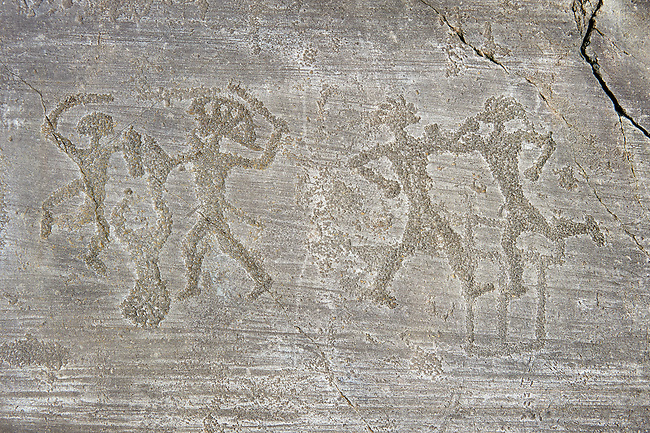 Petroglyph, rock carving, of two warriors boxing and two warriors fighting with swords and small shields, one is wearing a headress. Carved by the ancient Camunni people in the iron age between 1000-1200 BC. Rock no 6, Foppi di Nadro, Riserva Naturale Incisioni Rupestri di Ceto, Cimbergo e Paspardo, Capo di Ponti, Valcamonica (Val Camonica), Lombardy plain, Italy