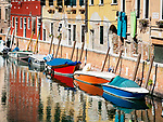 Canal and colorful boats, residences, Venice, Italy.