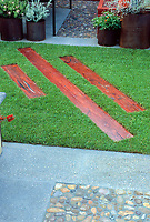 Pretty colored ornamental wood planks in lawn reduce lawn grass surface, add tread and add interest
