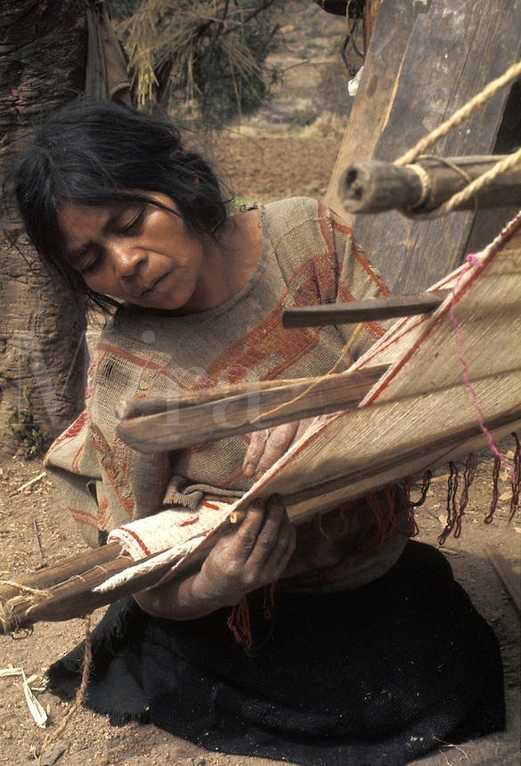 Latin America, Mexico, Oaxaca State, Mixtec Indian woman weaving cotton cloth using backstrap loom..