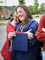 Linda Goggans (from left) hugs her daughter Chaney Goggans, Friday, May 15, 2020 during a graduation ceremony at The New School in Fayetteville. The New School celebrated its first graduation in a hybrid virtual/in-person ceremony. <br /> <br /> The senior class consisted of 11 students. The ceremony was conducted outdoors where graduates and their families, the only guests in attendance outside of essential faculty and staff, were restricted to spaces within safe social distances to view pre-recorded programming and to allow graduates to accept their diplomas one at a time. Check out nwaonline.com/200516Daily/ for today's photo gallery. <br /> (NWA Democrat-Gazette/Charlie Kaijo)