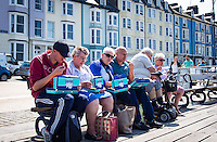 UK Weather: Aberystwyth, Ceredigion, West Wales Thursday 12th May 2016. <br />A group of people take in the view and the warm weather whilst they stop for their lunch of fish & chips on the promenade