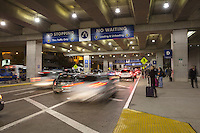Passengers wait for rides at the passenger drop off level, Austin–Bergstrom International Airport (ABIA) - Stock Image.