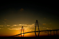 06/28/07:  Sunset view of the Cooper River Bridge in Charleston, SC. The bridge, also called the Arthur Ravenel Jr. Bridge, is a cable-stayed bridge over the Cooper River in South Carolina. The eight-lane bridge connects downtown Charleston to Mount Pleasant. ..When it opened in 2005, the Cooper River Bridge replaced two obsolete cantilever truss bridges. With a main span of 1,546 feet (471 m), the bridge is longest among cable-stayed bridges in the Western Hemisphere and currently is the longest cable stay bridge on the East Coast of the United States. It was designed by Parsons Brinckerhoff. ..
