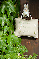 A sweet paded fabric sign welcoming one into the garden hangs from a door handle in the shape of a fly