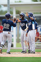 GCL Rays Jose Tonton (22) is greeted by Jesus Sanchez (center), Gilbert Marrero (right), and Kevin Santiago (back) after hitting a home run during the second game of a doubleheader against the GCL Red Sox on August 9, 2016 at JetBlue Park in Fort Myers, Florida.  GCL Rays defeated GCL Red Sox 9-1.  (Mike Janes/Four Seam Images)