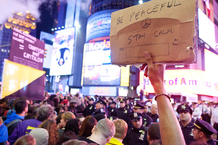 """Protesters with """"Occupy Wall Street"""" are blocked by barricades in Times Square on October 15, 2011 in New York City.  While crowd estimates numbered in the tens of thousands, police tactics (including nets, motor scooters, barricades, arrests, and intimidation by riders on horseback) prevented the crowd, which had been split up, from joining together as one in the middle of Times Square."""