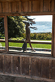 USA, California, Big Sur, Esalen, a reflection of a woman walking infront of the Bookstore with the Pacific Ocean in the distance, the Esalen Institute