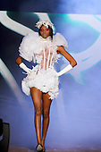 Model walking down the catwalk in a white transparent corset style dress created by Helmer