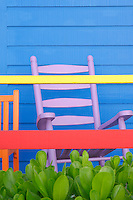 A pink rocking chair has been placed against the blue clapboard wall of a beach hut