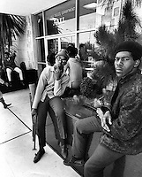 Black Panthers 17 yr-old Bobby Hutton (with shotgun) and Reginald Forte in front of the Oakland Police Dept. Jail protesting treatment by police. (1967 photo by Ron Riesterer)<br />