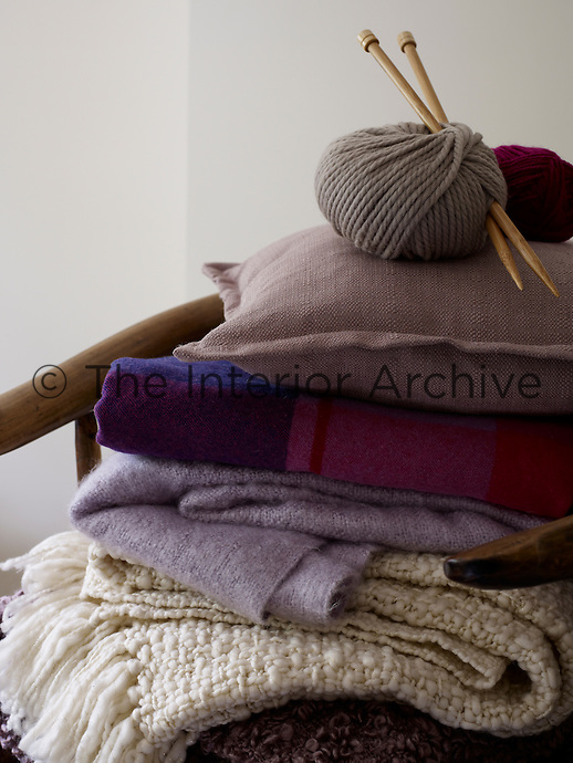 Interior image in a location house shows a pile up of blankets, fabrics, a cushion and balls of yarn with knitting needles attached. Styling by Alice King.