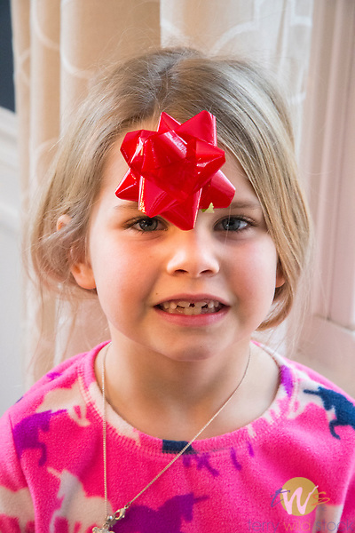 Child with Christmas ribbon on forehead.