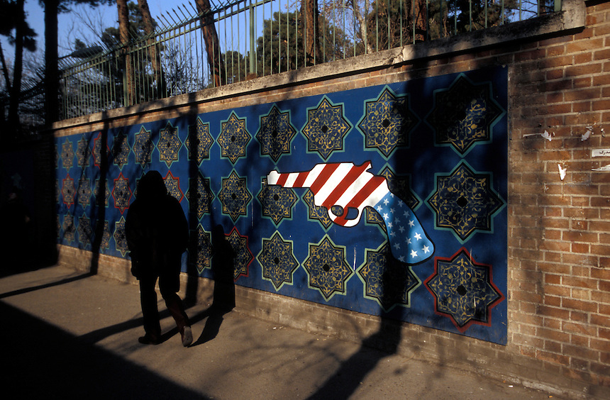 An Iranian man walks by an anti-United States mural outside the former American embassy in Tehran. The embassy building was abandoned after the 1979-1981 Iranian Hostage Crisis.  Photo: Ed Giles.