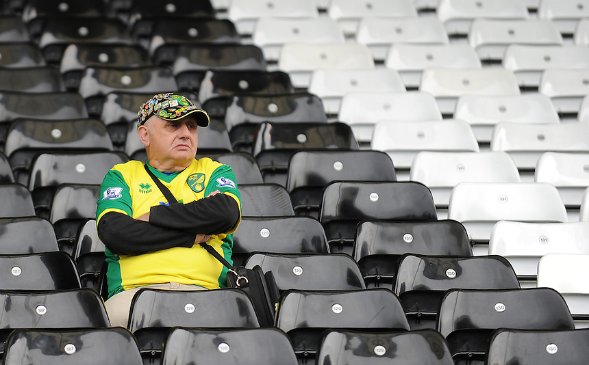 A dejected Norwich City fan at Craven Cottage, home of Fulham<br /> <br /> Photo by Ashley Western/CameraSport<br /> <br /> Football - Barclays Premiership - Fulham v Norwich City - Saturday 12th April 2014 - Craven Cottage - London<br /> <br /> &copy; CameraSport - 43 Linden Ave. Countesthorpe. Leicester. England. LE8 5PG - Tel: +44 (0) 116 277 4147 - admin@camerasport.com - www.camerasport.com