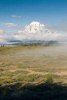 snow-capped Mt. Moran emerges from the fog at sunrise