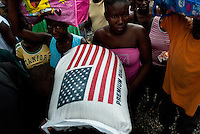 A Haitian woman carries a bag of the US rice in the La Saline market, Port-au-Prince, Haiti, 14 July 2008. Every day thousands of women from all over the city of Port-au-Prince try to resell supplies and food from questionable sources in the La Saline market. The informal sector significantly predominate within the poor Haitian economics and the regular shops virtually do not exist. La Saline is the largest street market area in Port-au-Prince.